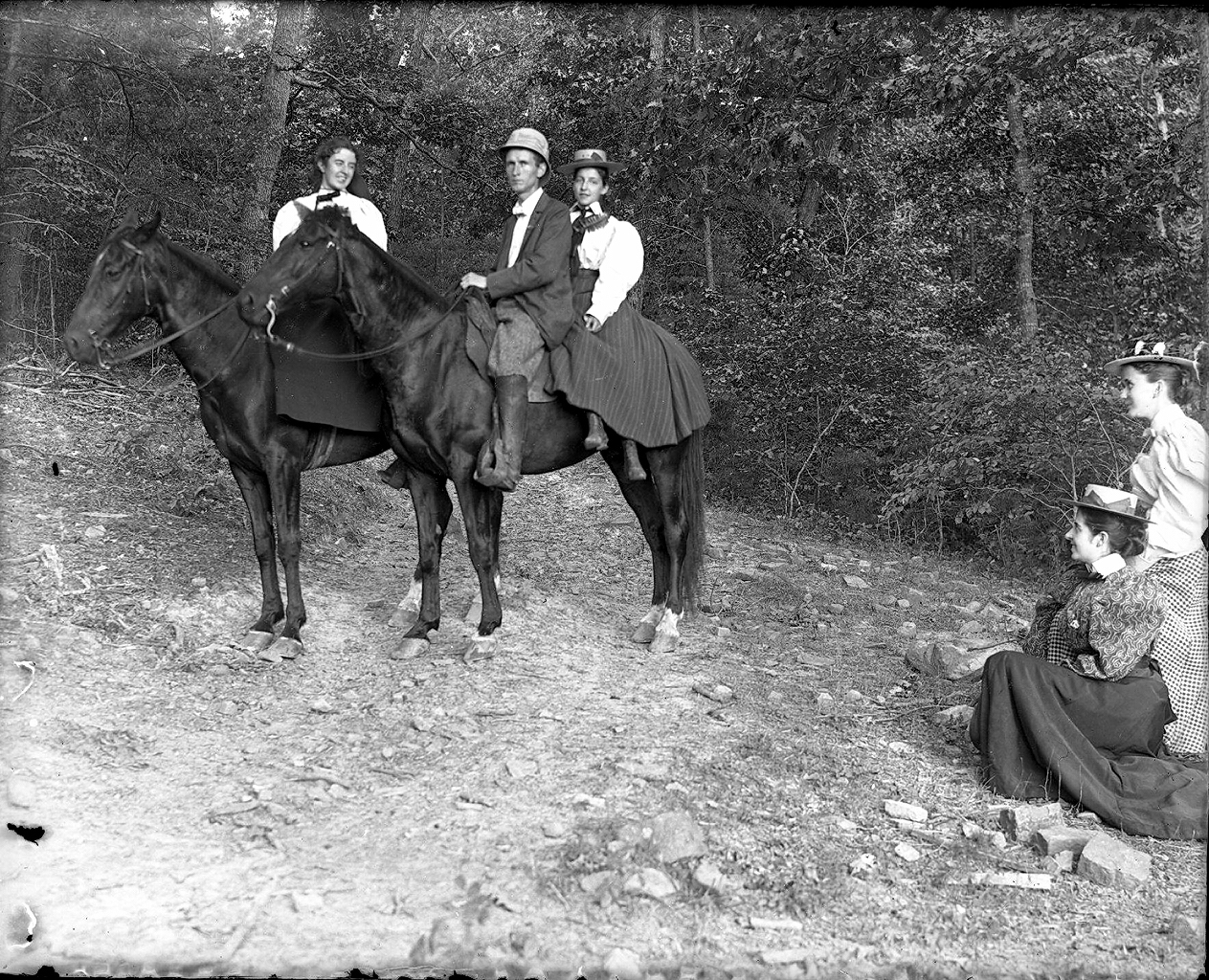 IMage of Susan and John, Jr. on horseback with young lady behind John, Jr. and two other ladies nearby