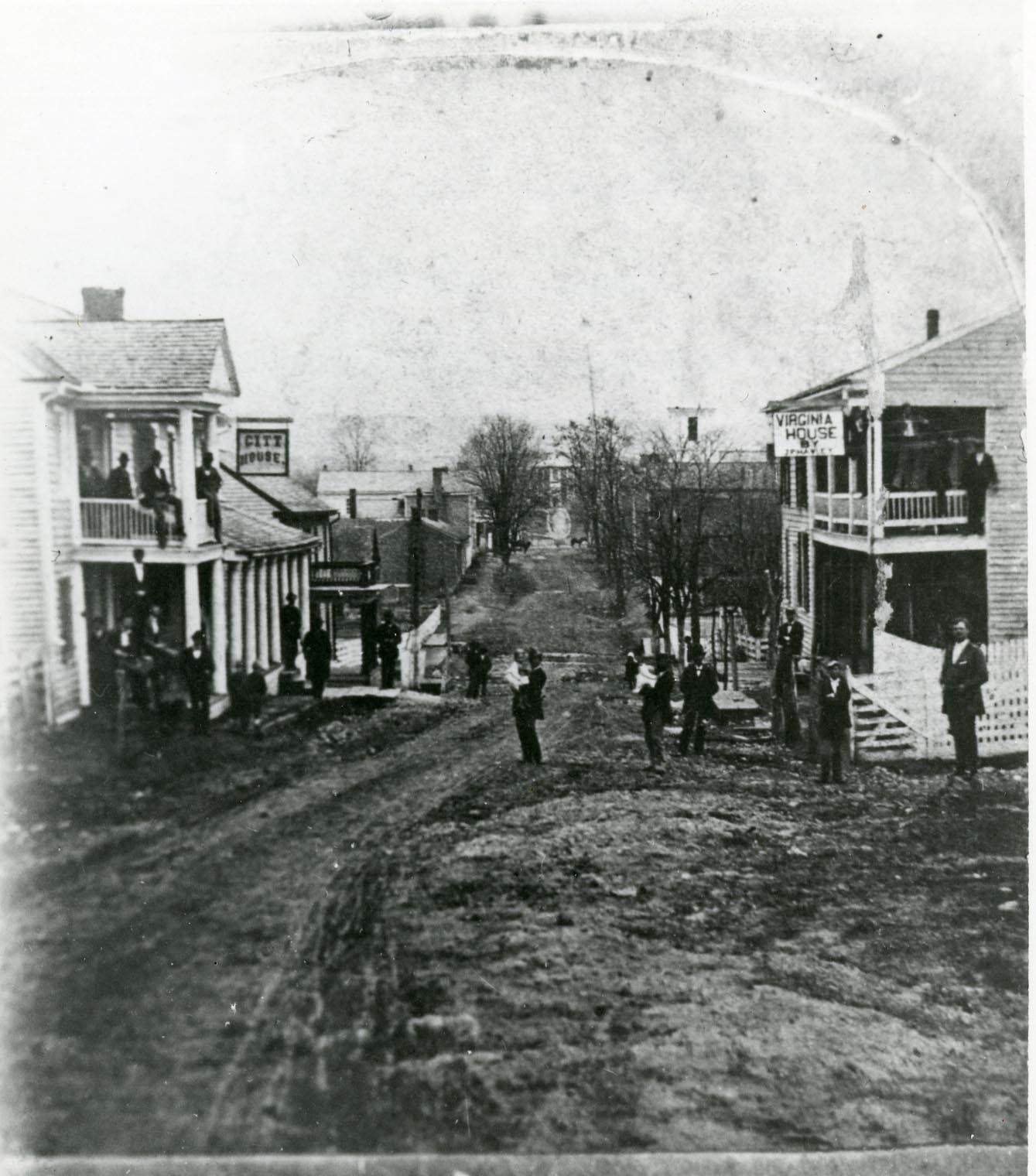Far int he distance at the center of the frame is the VAMC machine shop. This photograph was taken on Main St. looking west, possibly near the Post Office.