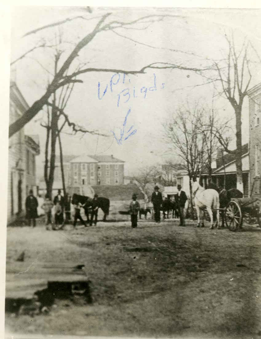 Before 1900, Main St. saw its fair share of horse traffic. This photograph was taken from the road, looking at the old Preston and Olin Building/then VAMC machine shop.