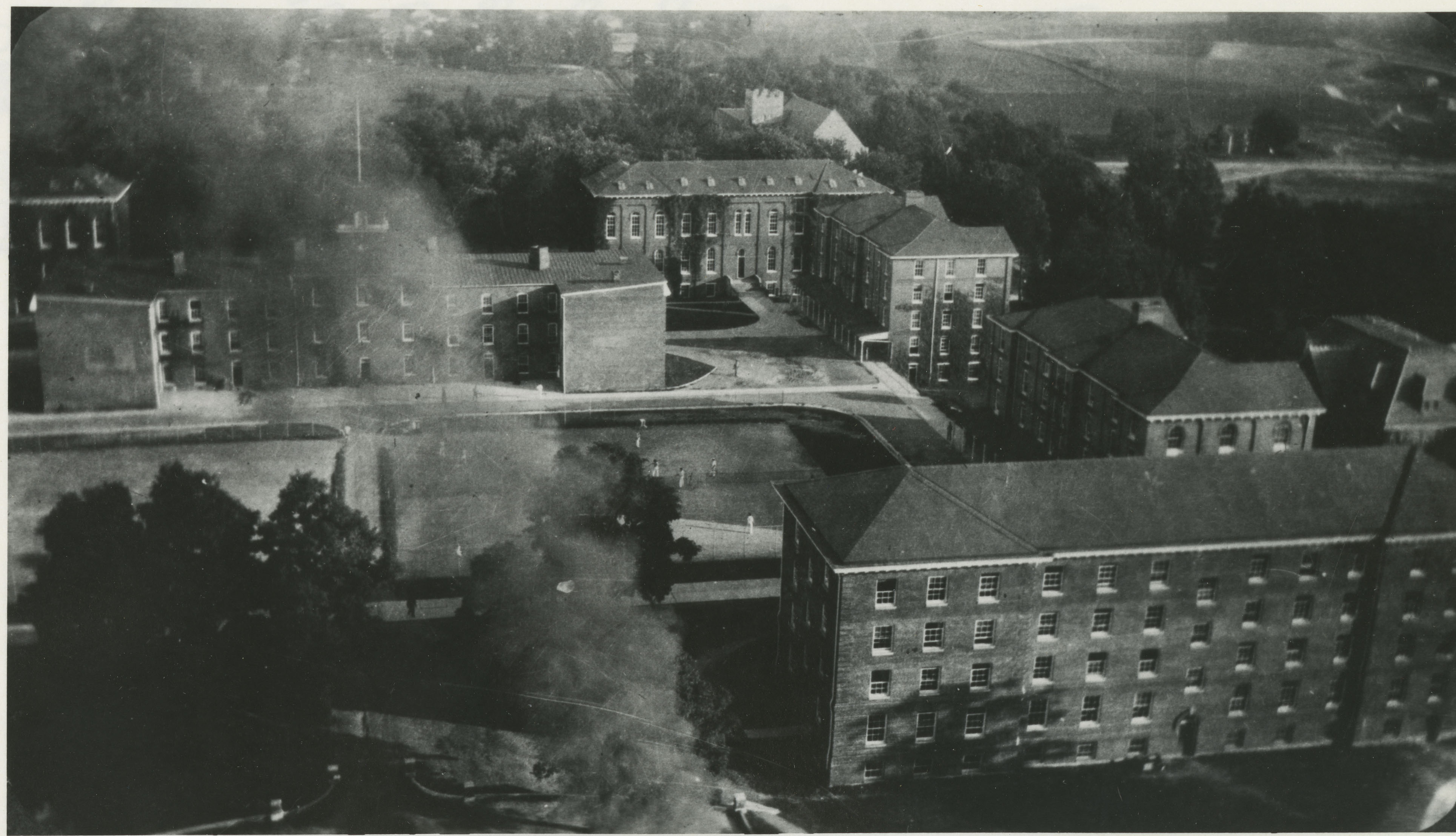 """Looking south from the tall smokestack of the new powerplant. Barracks No. 1 at left center. Clockwise around Barracks No. 1, starting at the top left: First Academic Building, Second Academic Building, Barracks No. 3 [part of the former Brodie Hall], Barracks No. 5, Barracks No. 6."" You can also see part of the old library at the top center."