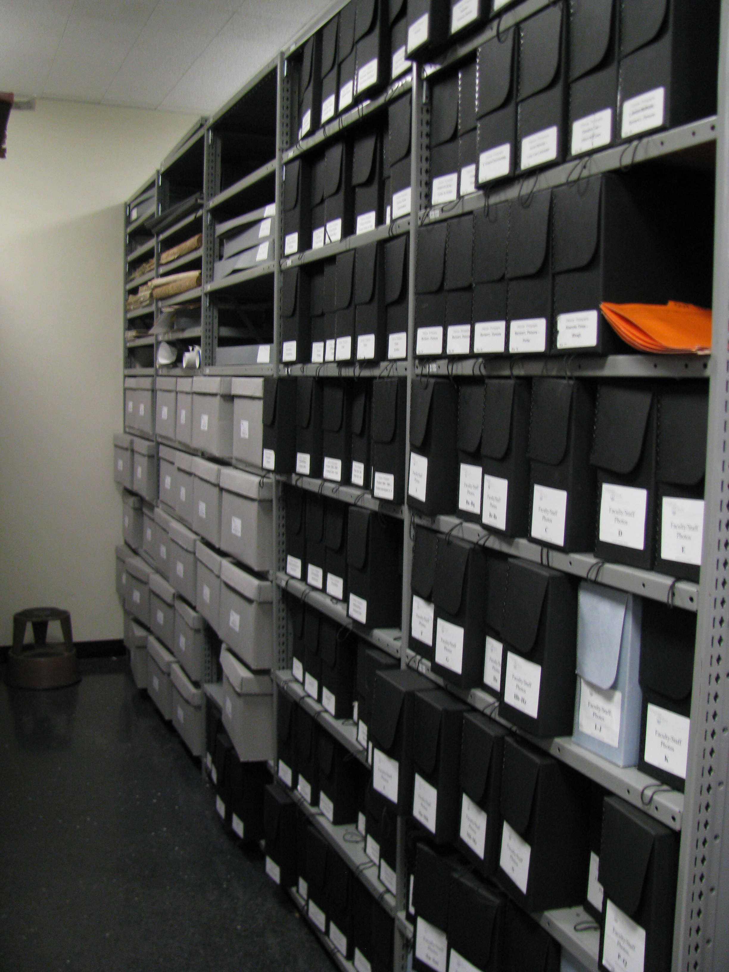 Our historical photograph collection is in black acid-free boxes and is organized generally by topic. Beyond it, you can see some bound and boxed newspapers above and part of our collection of vertical files on university history.