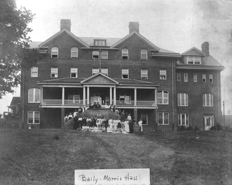 Black and white photograph of Baily-Morris Hall, a building on the campus of Christiansburg Industrial Institute. Several African American teachers stand on a staircase in front of the building.