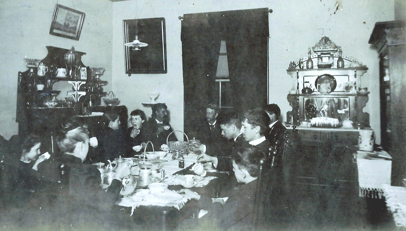 Image of family at dining table in a room with two sideboards and a china cabnet