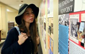 Photograph of a female-presenting person wearing a blue open knit sweater and black felt cloche hat holding a light blue backpack. This person is viewing the exhibit posters displayed on a wall.
