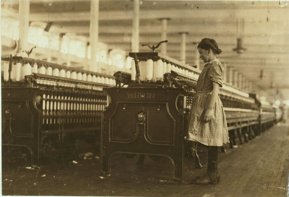A young girl with her dark hair in a bun wearing a dress, stockings, and leather shoes monitors a bank of cotton spinning machines in the mill.